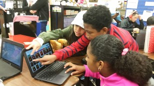 Image of students working with a laptop.